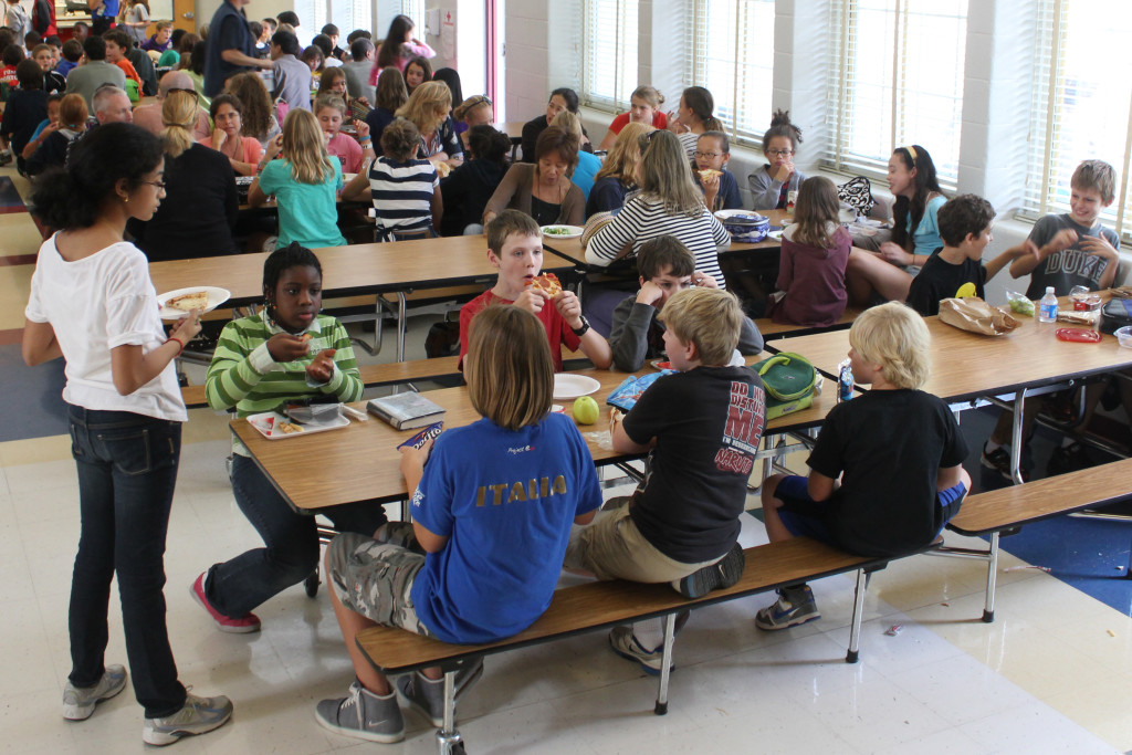 Kids eat in a school lunch room.