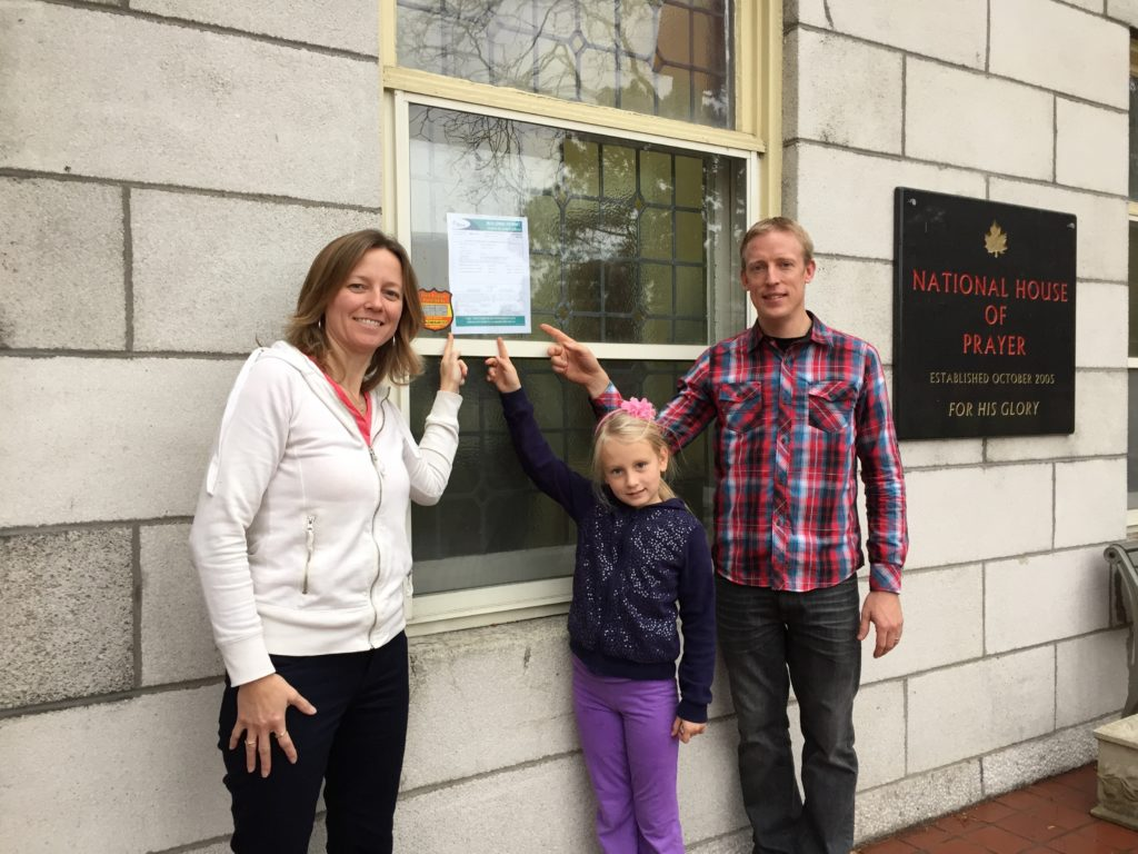 Ken, Deb, and Olivia point to the building permit.