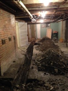 An unfinished basement with a gaping hole cut in the floor.