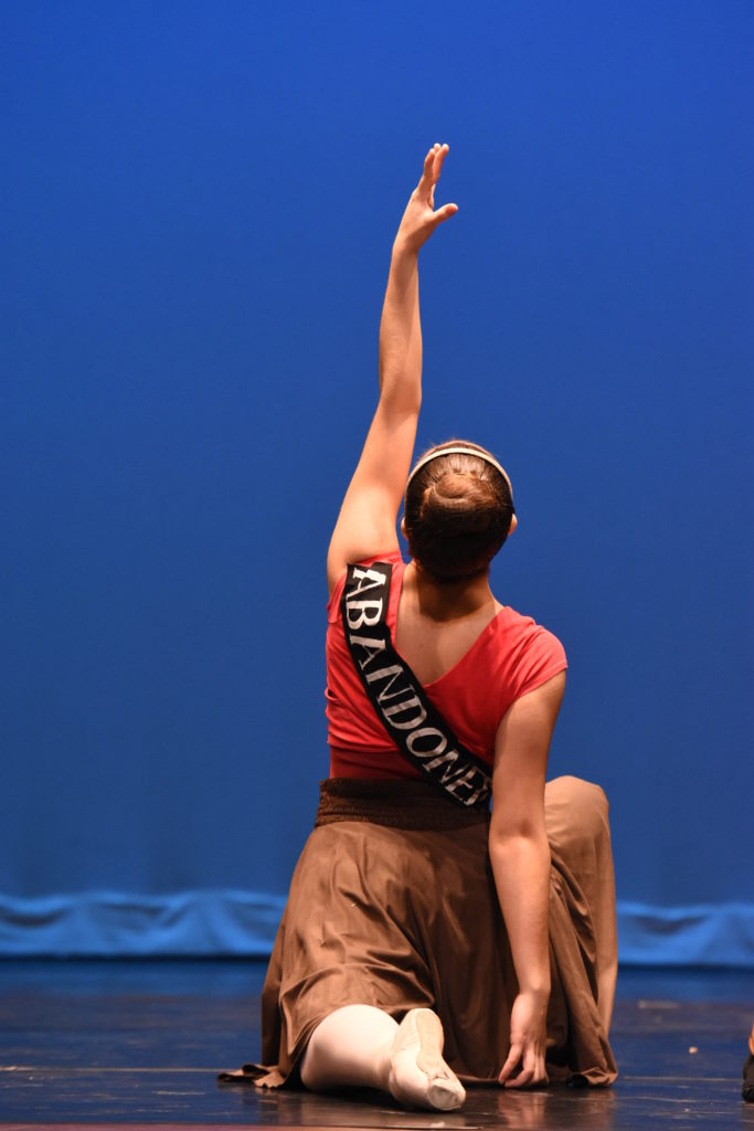 """A dancer kneels. The word """"abandonment"""" is across her back."""