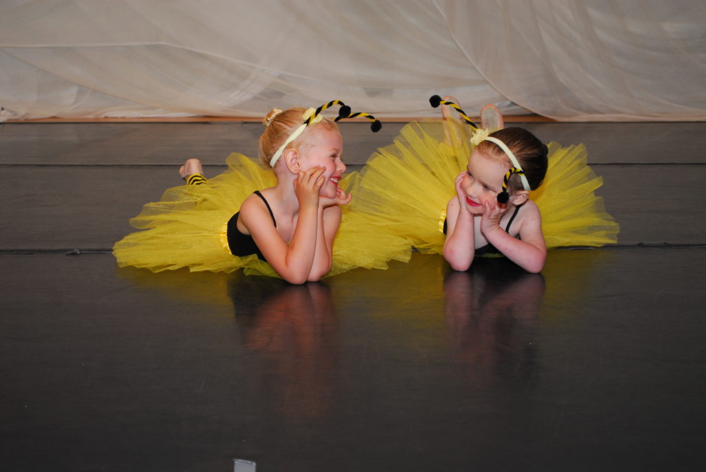 Two young dancers smile at each other.