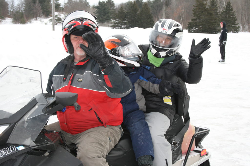 Three people ride a snowmobile.