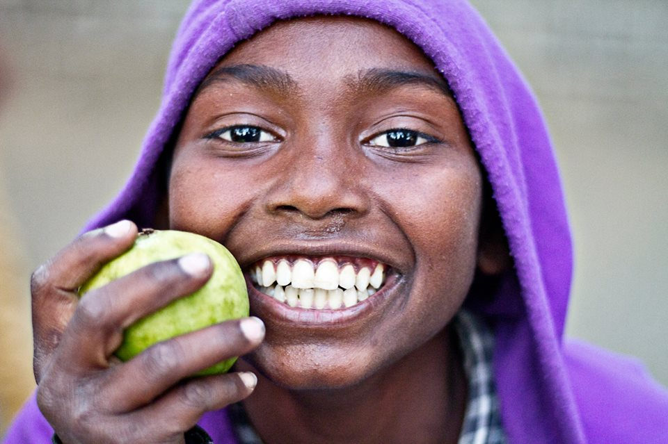 A child smiles widely while eating an apple.