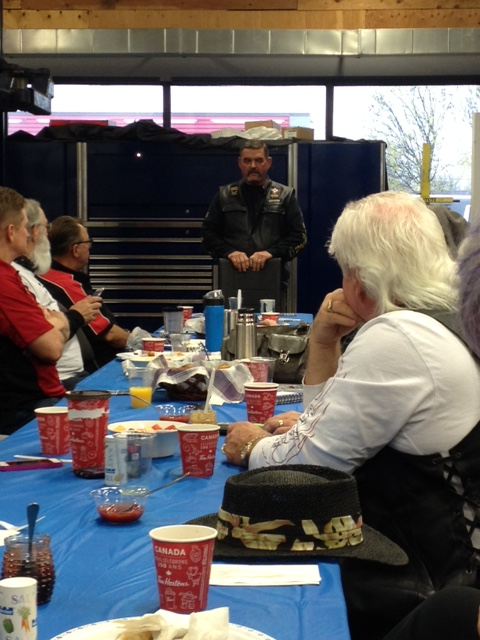 Erwin Andrews speaks to a group around a table.