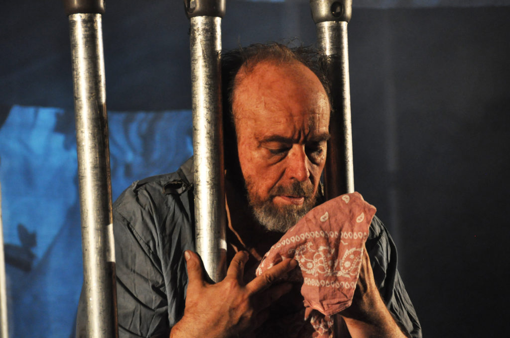 A man holds a cloth through the bars of a prison cell.