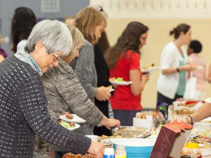 Women get food at a potluck.