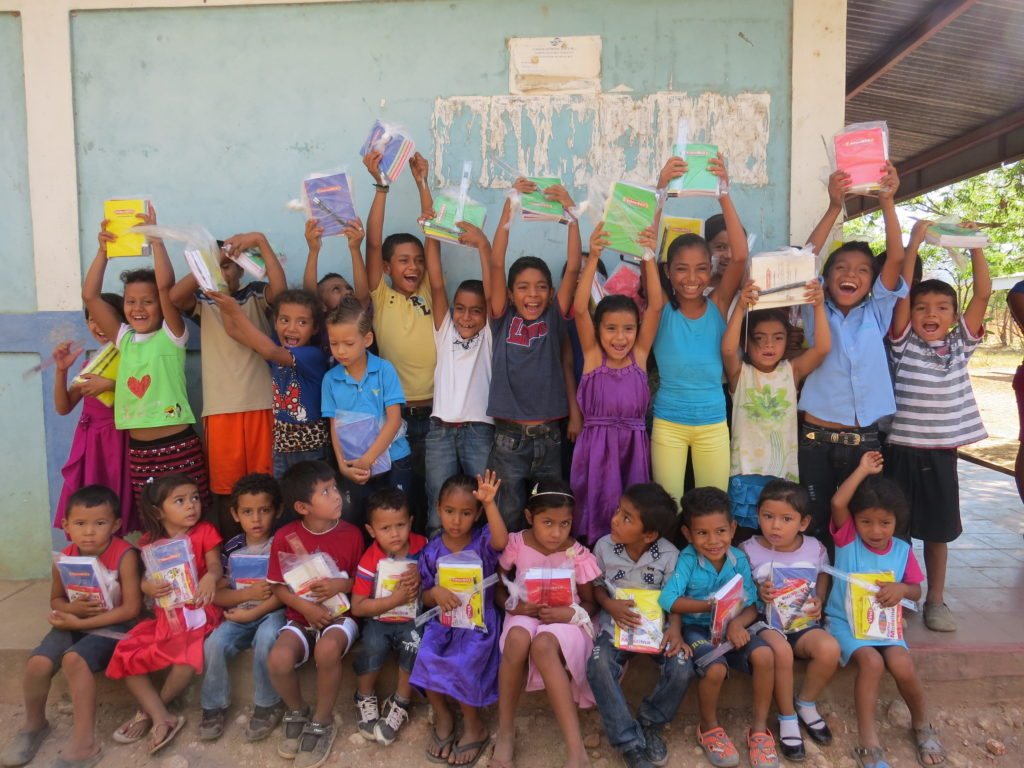 Kids hold up notebooks and school supplies.